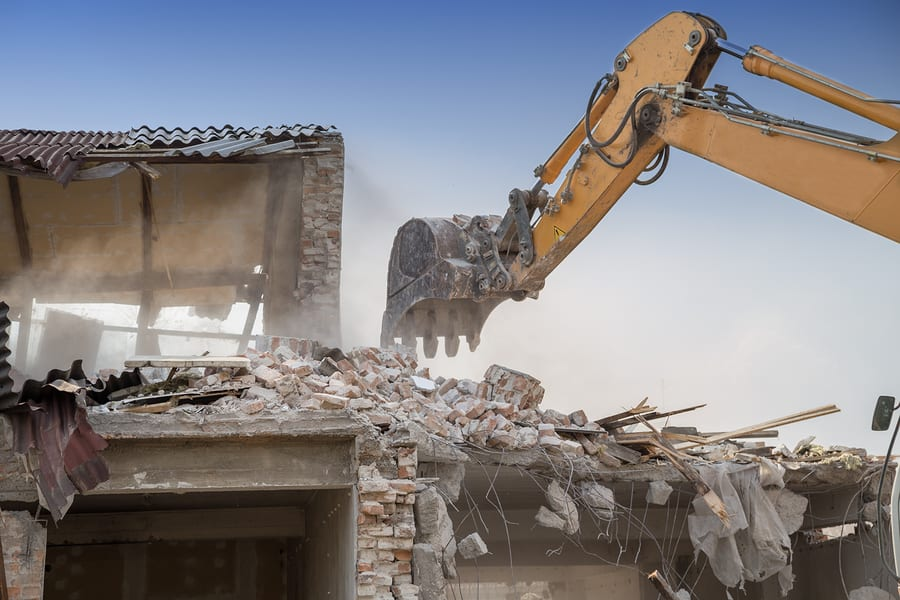 Close up of building demolition by excavator arm. Backhoe demolishing house.
